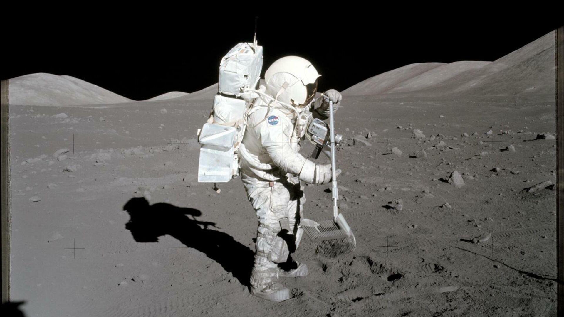 Астронавт и геолог миссии Аполлон-17 Харрисон Шмитт в 1972 году собирает образцы лунного грунта, которые использовались в данном исследовании - РИА Новости, 1920, 26.10.2020