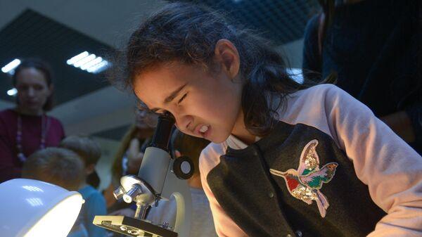 Девочка рассматривает материал под микроскопом