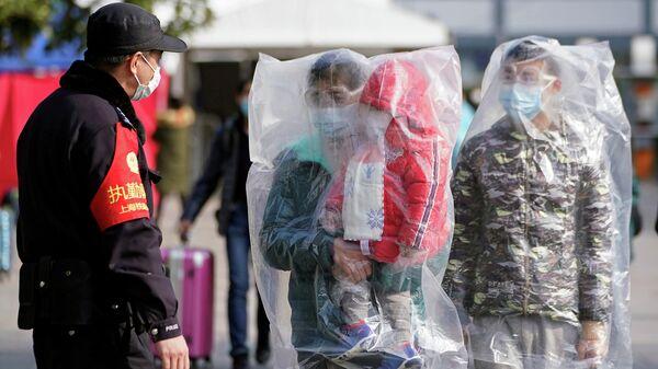 Пассажиры в масках и в полиэтиленовых пакетах на железнодорожном вокзале в Шанхае, Китай. 9 февраля 2020
