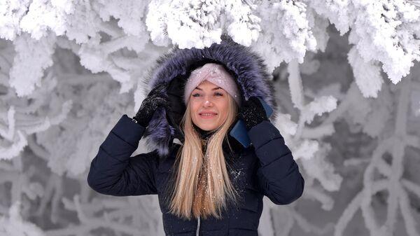 Женщина позирует для фото в заснеженном лесу на берегу реки Енисей