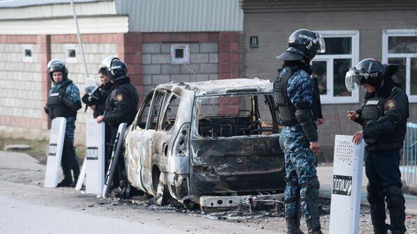 Сотрудники полиции у сгоревшего автомобиля на улице поселка Масанчи