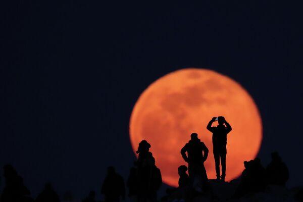 Люди наблюдают полнолуние с холма Ареопаг в Афинах, Греция