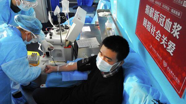 Пациент, выздоровевший после заболевания коронавирусом, сдает кровь в больнице китайского города Ляньюньган