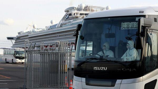 Автобус с пассажирами круизного лайнера Diamond Princess покидает терминал в порту Йокогама