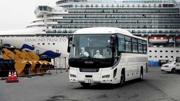 Автобус выезжает из терминала в порту Йокогама, в котором находится круизный лайнер Diamond Princess