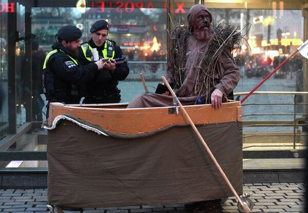 Полицейские с протестующим во время демонстрации за улучшение климата на карнавальном шествии Geisterzug в Кельне, Западная Германия