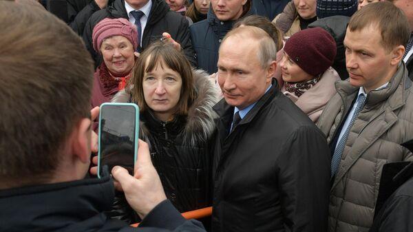 Президент РФ Владимир Путин фотографируется с жителями города после церемонии возложения цветов к памятнику первому мэру Санкт-Петербурга Анатолию Собчаку