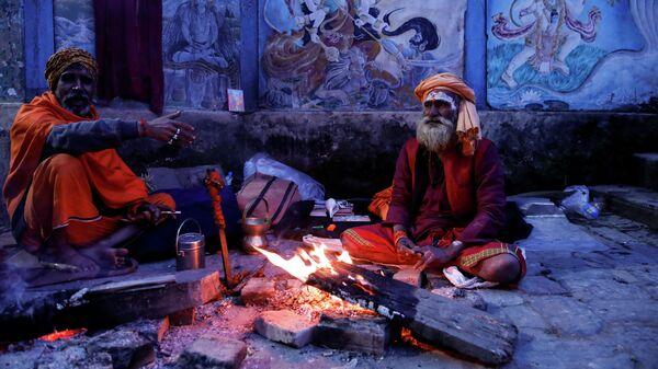 Cадху, сидят у костра в храме Пашупатинатха за день до начала фестиваля Шиваратри в Катманду, Непал