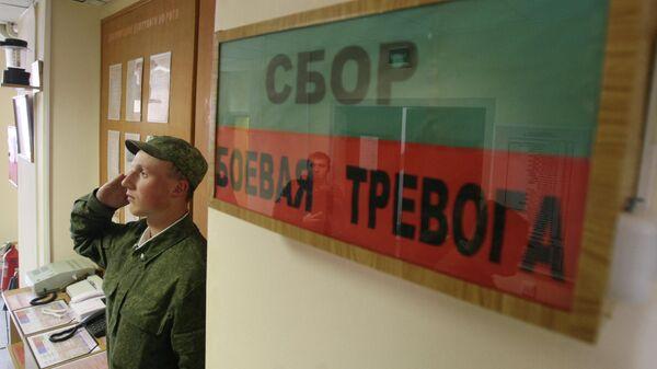 Военнослужащий отдает честь у входа в казарму общевойсковой отдельной мотострелковой бригады Западного военного округа, дислоцированной в поселке Каменка Ленинградской области.