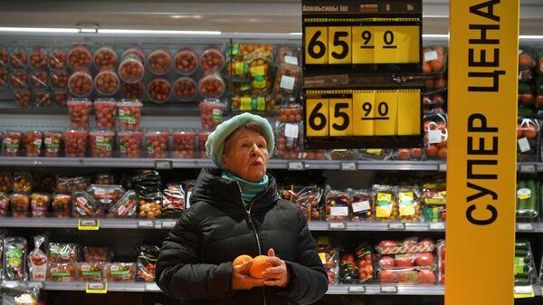 Женщина выбирает апельсины в супермаркете Перекресток в Москве