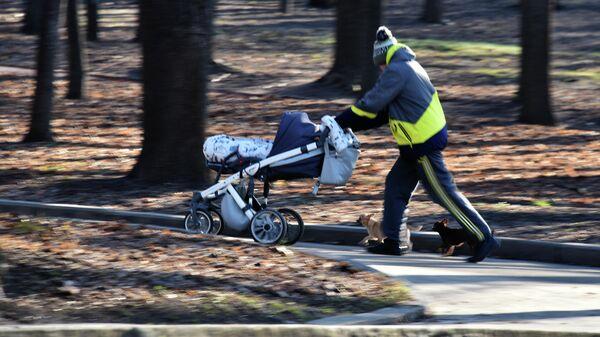 Мужчина с детской коляской гуляет по парку