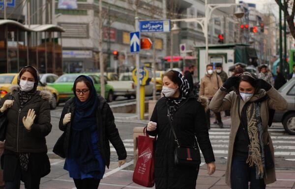 Жители Тегерана идут по одной из центральных улиц в медицинских масках