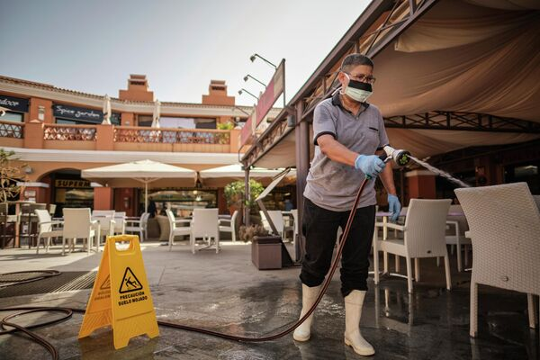Сотрудник в маске моет террасу торгового центра в Ла Калета, Тенерифе