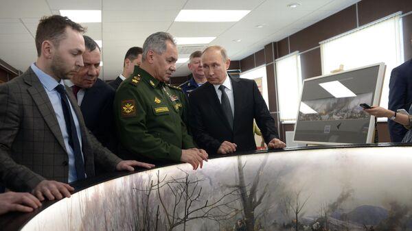 Верховный главнокомандующий, президент РФ Владимир Путин и министр обороны РФ Сергей Шойгу осматривают макет - реконструкцию высоты, на которой произошло противостояние бойцов 6-й роты и боевиков