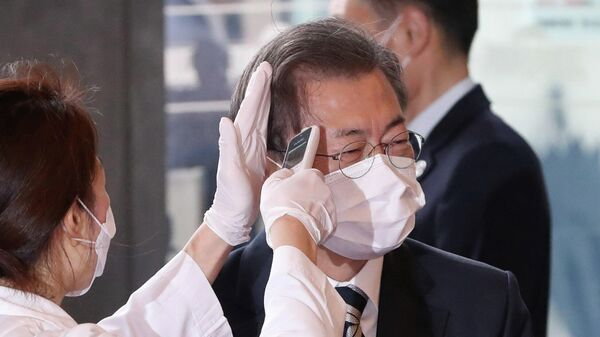 Медицинский работник измеряет температуру президенту Южной Кореи Мун Чжэ Ину, прибывшему на Национальную ассамблею в Сеул