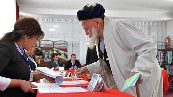 Житель Душанбе получает бюллетень на избирательном участке, чтобы проголосовать на выборах в нижнюю палату парламента Таджикистана. 1 марта 2020