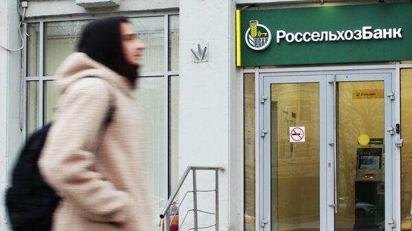 Прохожий около входа в офис банка Россельхозбанк на одной из улиц в Москве