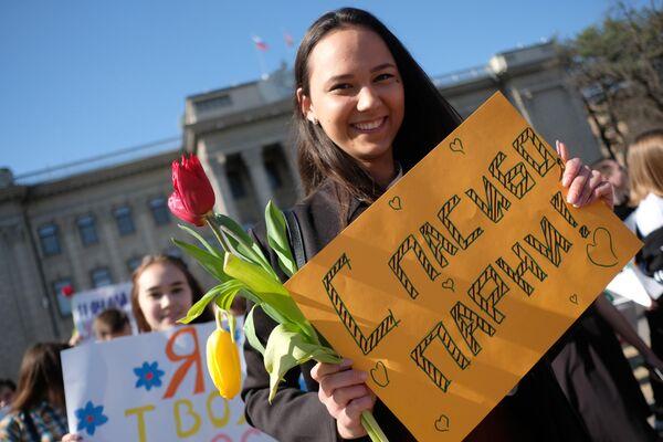 Участники флешмоба Цветы любимым! в рамках празднования Международного женского дня на Пушкинской набережной в Парке Горького в Москве