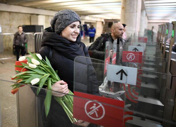 Девушка проходит через турникет в метрополитене