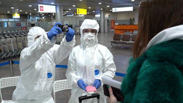 Медицинские работники проводят осмотр пассажиров в аэропорту Шереметьево