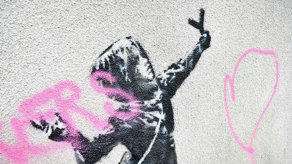 Разрисованная работа художника Бэнкси на стене дома на Марш-лейн в Бристоле