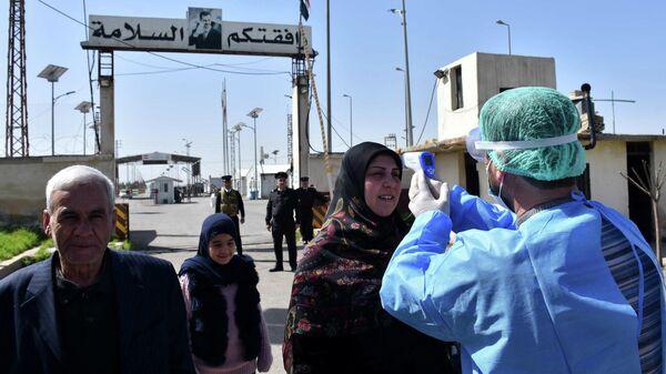 Измерение температуры в связи с распространением коронавируса на пограничном переходе в Сирии