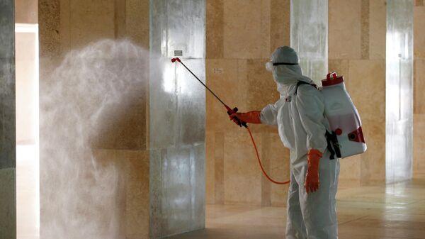 Персона распыляет дезинфицирующее средство в рамках борьбы с эпидемией коронавируса