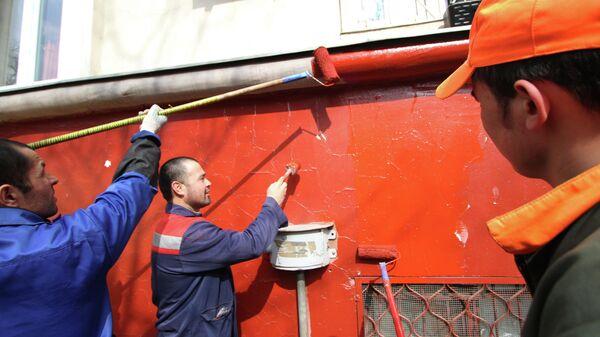 Сотрудники коммунальных служб красят фасад жилого дома