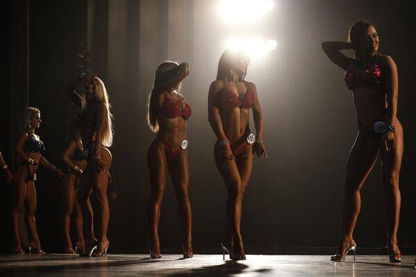 Участницы соревнований в номинации фитнесс-бикини во время выступления на Чемпионате Новосибирской области по бодибилдингу
