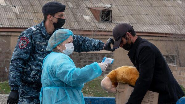 Медицинский работник проверяет температуру у прохожего в армянском Вагаршапате
