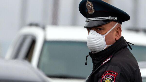 Сотрудник правоохранительных органов в защитной маске в Ереване