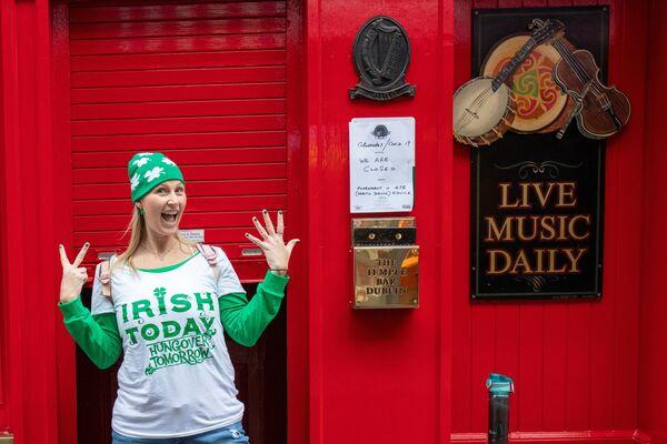 Женщина позирует возле закрытого паба в Дублине в День святого Патрика