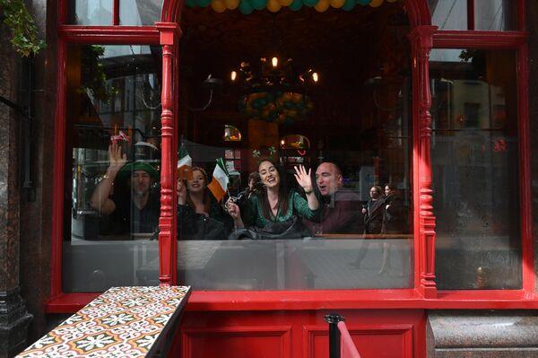 Люди смотрят в окно паба в центре Лондона в День святого Патрика