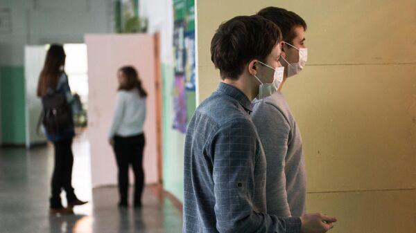 Дети в защитных масках в одной из школ Омска. В связи с эпидемией гриппа и ОРВИ все школы и детские сады Омска закрыты на карантин