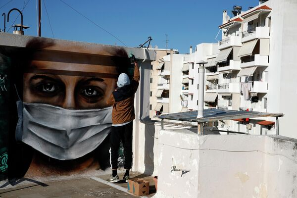 Художник рисует граффити на крыше дома в Афинах