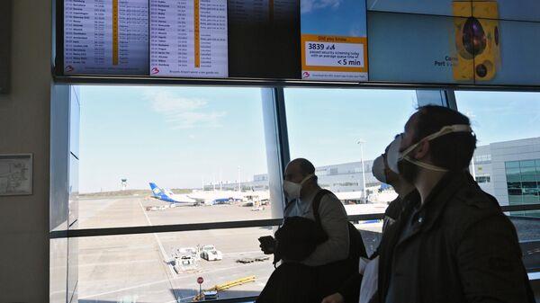 Пассажиры в медицинских масках в аэропорту Брюсселя