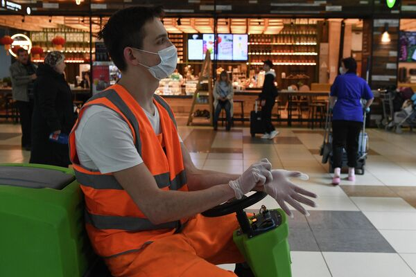 Сотрудник клининговой службы в медицинской маске в аэропорту Толмачево в Новосибирске