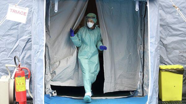 Медицинский работник у входа в больницу Spedali Civili в городе Брешиа, Италия