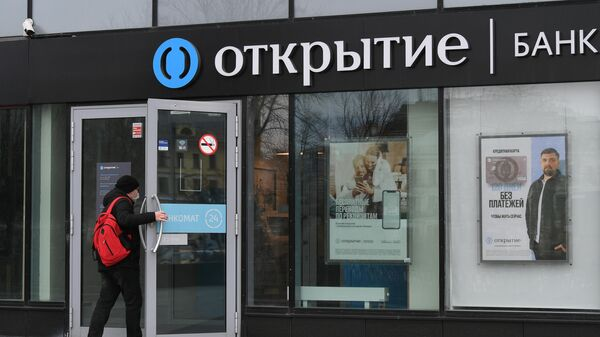 Посетитель заходит в отделение банка Открытие на одной из улиц в Москве