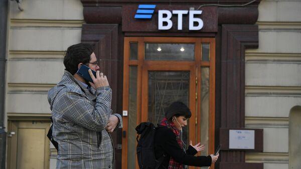 Прохожие у отделения банка ВТБ на одной из улиц в Москве