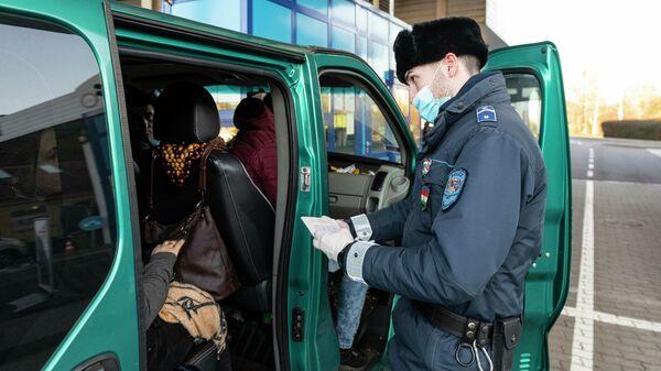 Сотрудник венгерской полиции проверяет документы украинских рабочих, покидающих Венгрию на пограничном пункте в городе Захонь, северо-восточная Венгрия