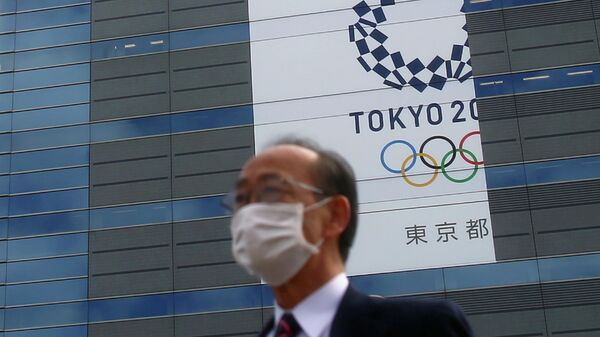 FILE PHOTO : A man, wearing a protective mask following an outbreak of the coronavirus disease (COVID-19) is pictured in front of a banner for the upcoming Tokyo 2020 Olympics in Tokyo, Japan, March 12, 2020. REUTERS/Edgard Garrido/File Photo