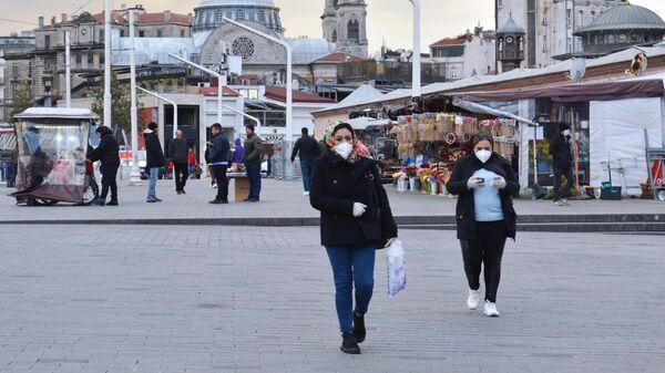 Прохожие в медицинских масках на одной из улиц в Стамбуле