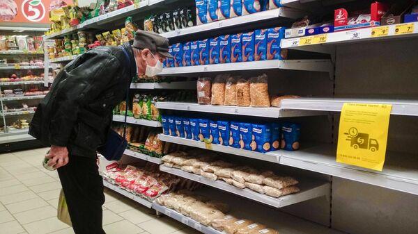 Мужчина выбирает товары в магазине Пятерочка в Москве