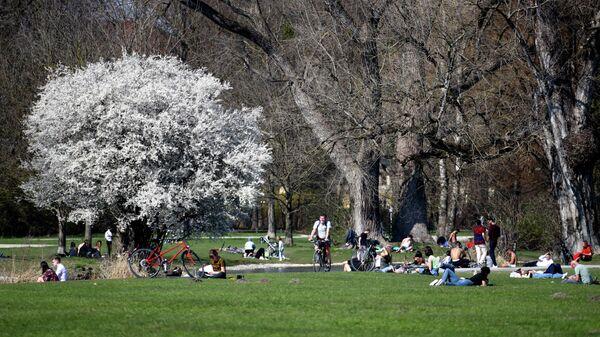 Посетители в парке Английский сад в Мюнхене, Германия