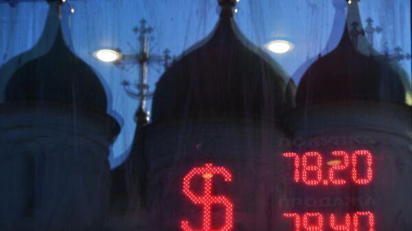 Отражение куполов церкви в окне и табло курса обмена доллара к рублю