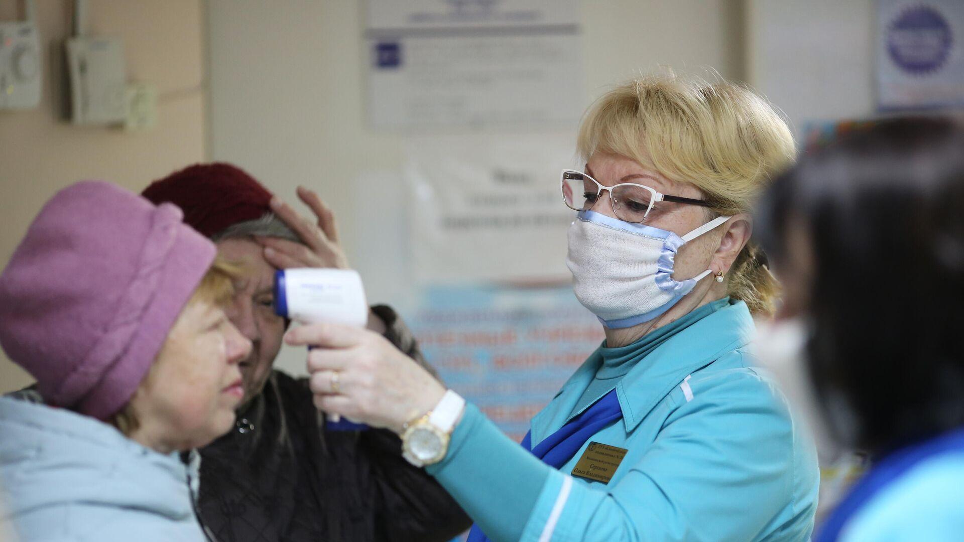 Сотрудница поликлиники  измеряет температуру посетительницы в связи с угрозой распространения коронавируса - РИА Новости, 1920, 04.03.2021