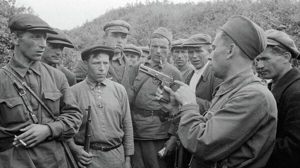 Командир партизанского отряда знакомит бойцов с оружием. Смоленская область, Россия