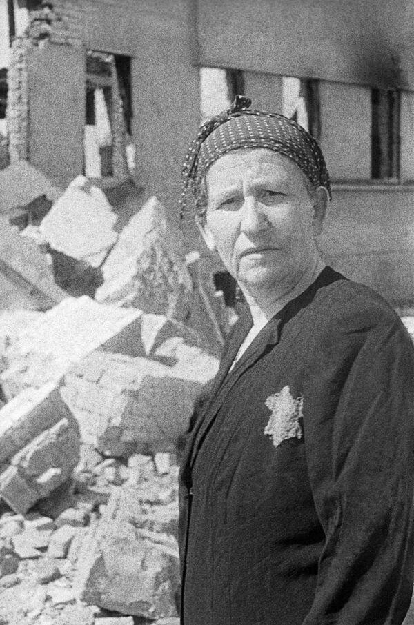 Жительница еврейского гетто на развалинах родного дома