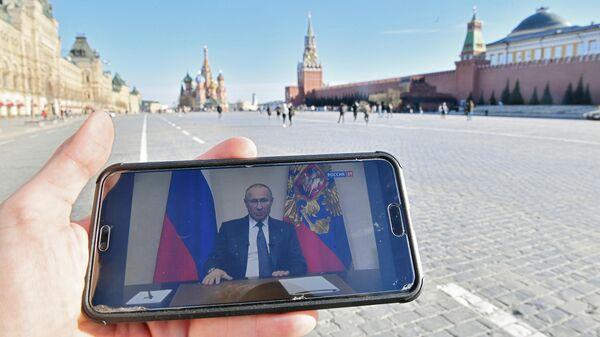 Житель Москвы смотрит на Красной площади со смартфона трансляцию обращения президента России Владимира Путина к гражданам из-за ситуации с коронавирусом